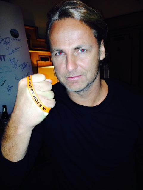 John Ewbank zegt: Ik STOP pesten Nu! met oranje bandje tegen pesten