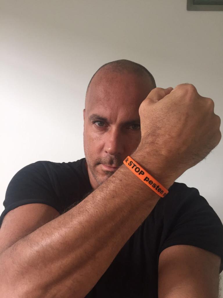Mental Theo zegt Stop Pesten Nu met oranje bandje tegen pesten